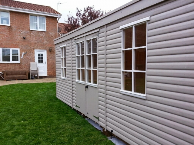 Summerhouse with shiplap cladding painted in light  lavendar/grey and white