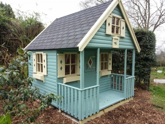 childrens wooden play house Shiplap cladding painted in seagrass with cream windows and detailing.