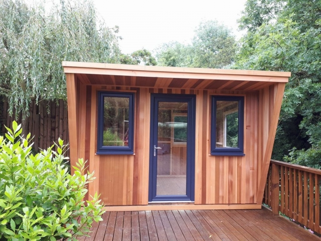 Cedar cladding on this pent roof summerhouse featuring an overhanging porch and fitted with UPVC windows and door.
