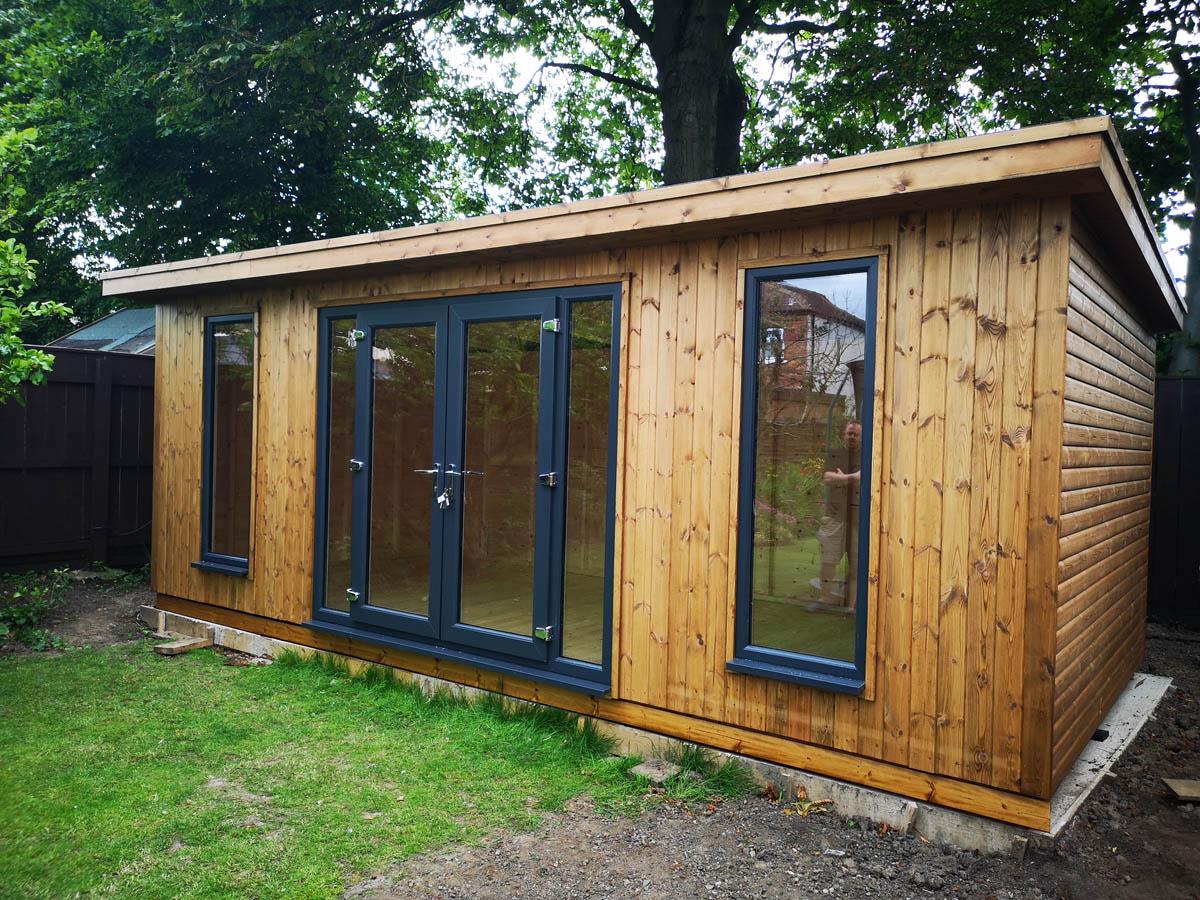 Large timber clad garden room with grey upvc door and windows